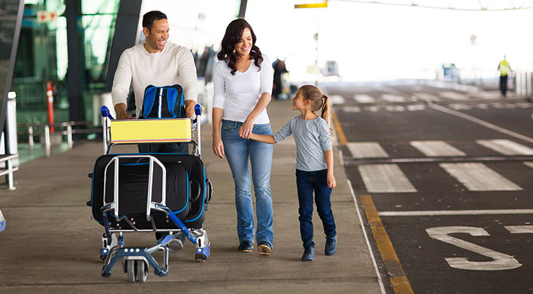 Family walking at airport with luggage