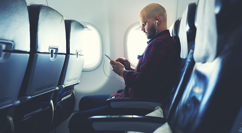 Man on plane listening to music on his phone